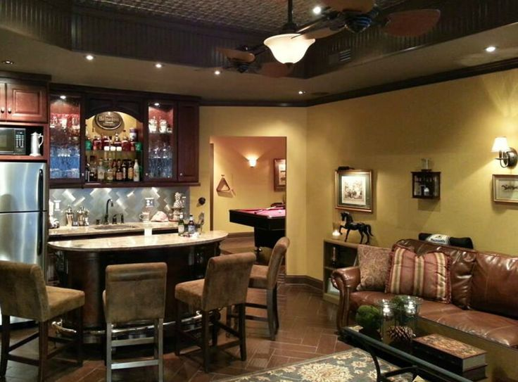 """This finished basement """"man cave"""" uses space very well, yet it's not too crammed. It includes a comfortable sitting area, mini-bar/kitchenette and pool table."""