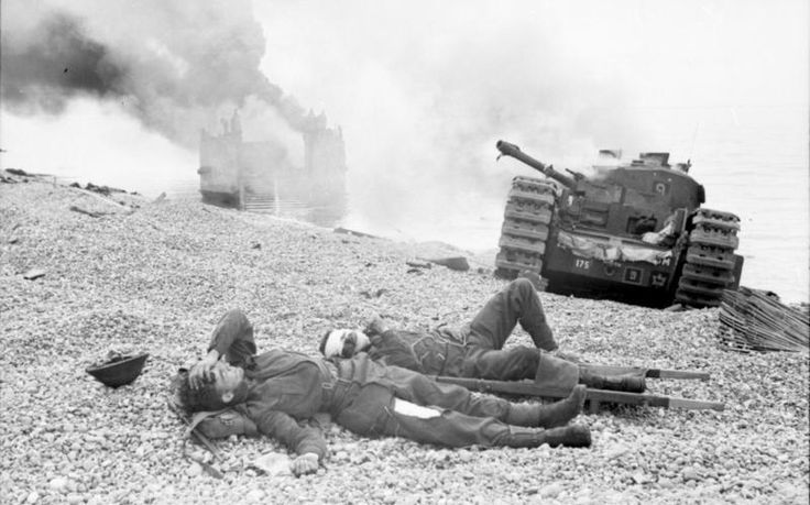 Dieppe, 1942: Canadian wounded and abandoned Churchill tanks after the raid. A landing craft is on fire in the background