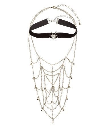 Velvet ribbon choker and short metal necklace. Choker with metal and rhinestone spider at front. Necklace with large spiderweb of metal chains at front with rhinestones at edges. Adjustable length, 13 3/4 - 17 in. and 17 3/4 - 22 1/2 in.