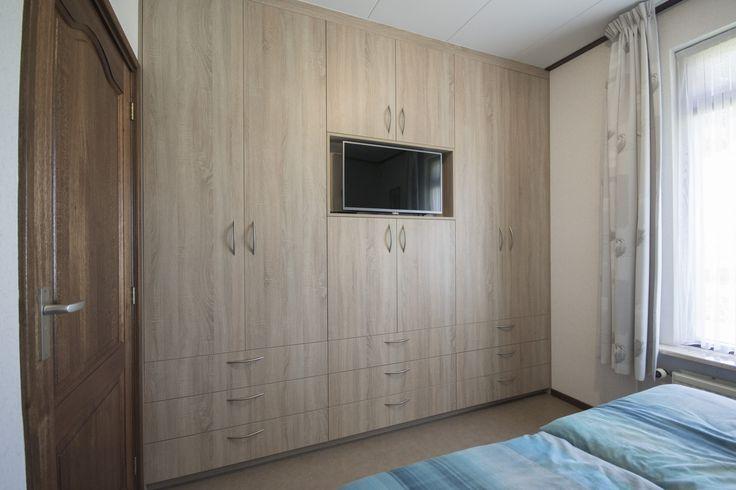 Slaapkamerkast, uitgevoerd in melamine met houtstructuur. Voorzien van een t.v. nis, 9 laden, 2 kledingliften en 2 uittrekbare schoenenrekken.