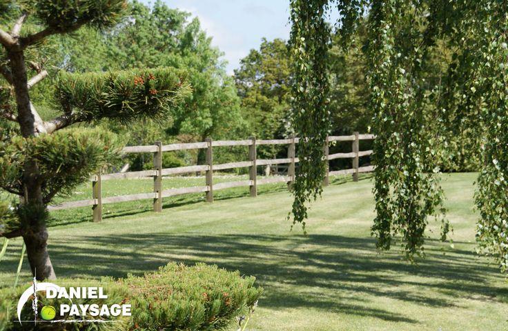 """Une clôture bois de style """"rétro"""" renforce le côté champêtre de ce jardin."""