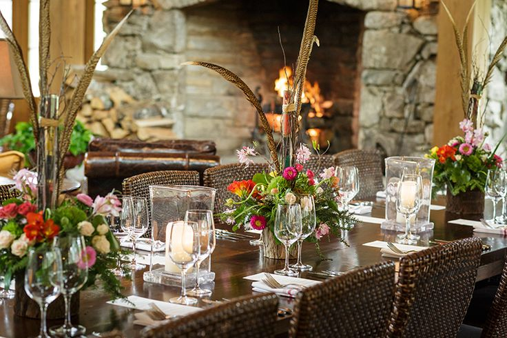 Rustic, spring table setting with local flowers and pheasant feathers in the mountains of North Carolina at Lonesome Valley. Floral design by Marcia McCarley.