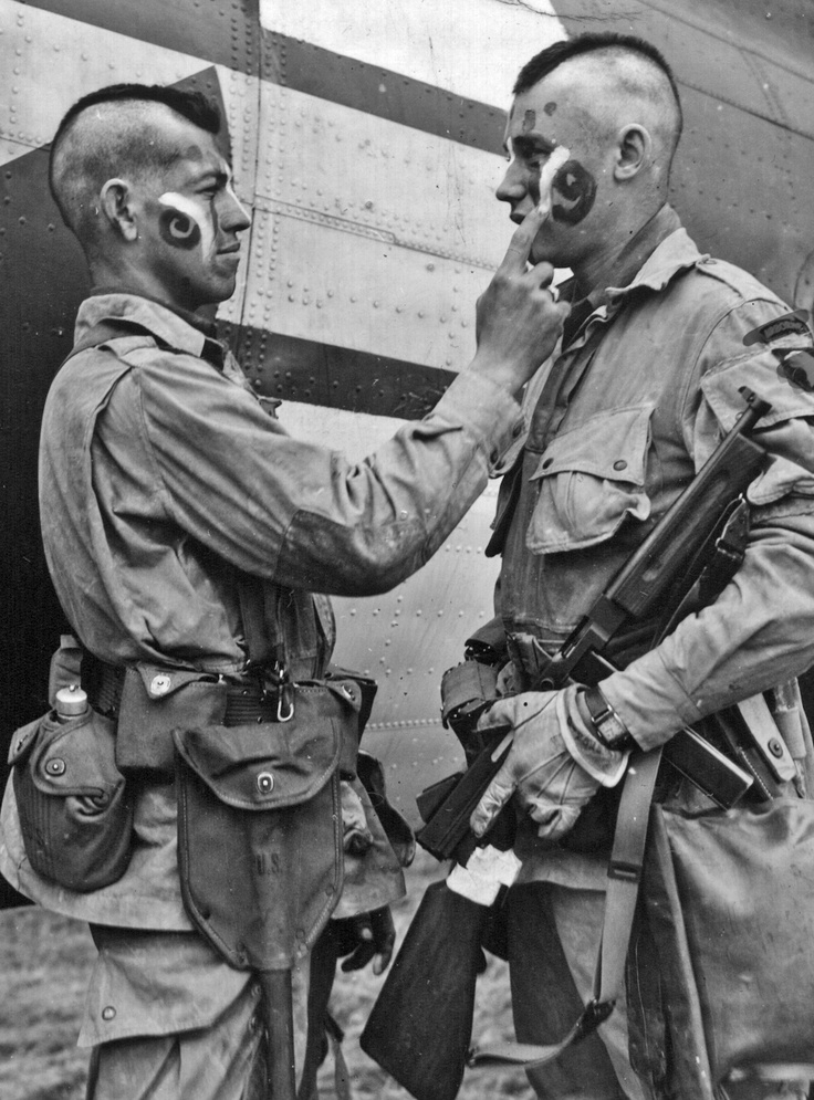 Paratroopers applying war paint Before being dropped into Normandy.
