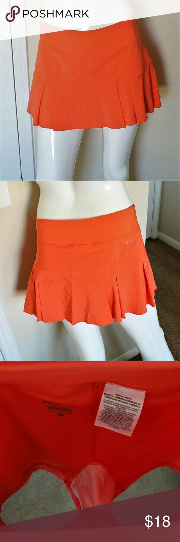 Nike Drifit Coral Tennis Skort Awesome workout skirt in gently used condition. It is fully lined with a pair of hidden shorts underneath. The photos make it seem a little brighter than it actually is. It's more coral and less bright orange. Can be used for tennis, badminton, golf, etc.   Please message me if you have questions or need more pictures. Nike Skirts Mini