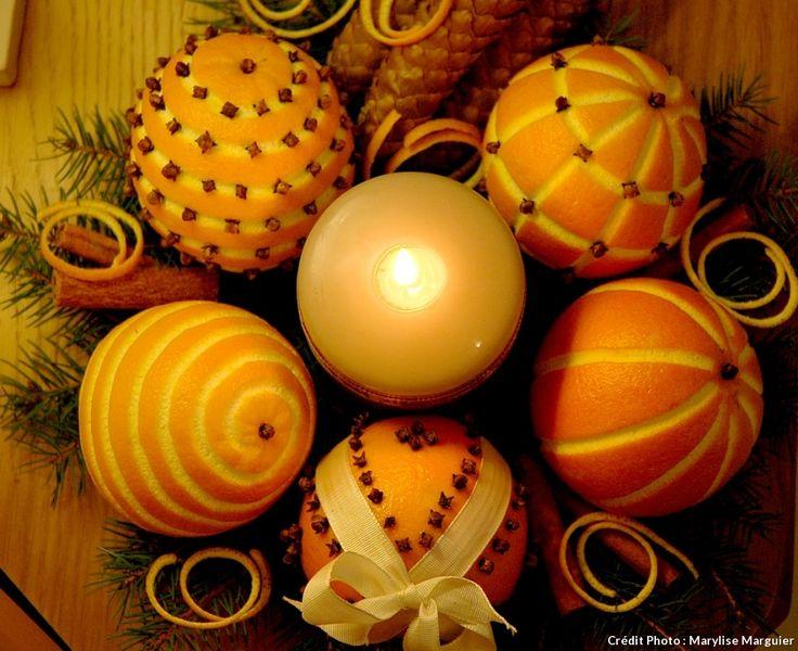 Oranges décorées sur une assiette décorée de branches de sapin, de pommes de pin, de bâton de cannelle, d'anis étoilé, de zeste d'orange... et d'une bougie au centre !
