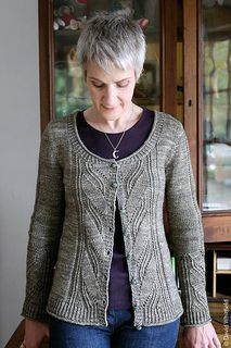 A feminine cardigan or pullover with a loose hem and high, A-line shape. Close-fitting through bust and sleeves, it features a panel of curling openwork leaves at center front and back, as well as on the lower sleeve. A short flare of twisted-rib trim edges the hem, sleeves, front bands, and scoop neck.