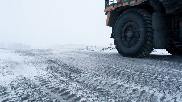Tipper or Dumper with Anthracite. Technology of Production Working in Winter by VisualBricks Mining dump truck driving on snowy road from coal cut in Siberia in Russia. Machinery for heavy industry carrying fossil and miner