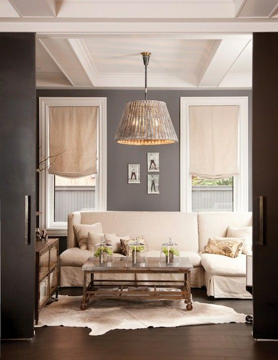 Shades of greys and creams. Textural light fixture & a wonderful ceiling detail..... Love that the designer used basic roman shades to dress the windows..