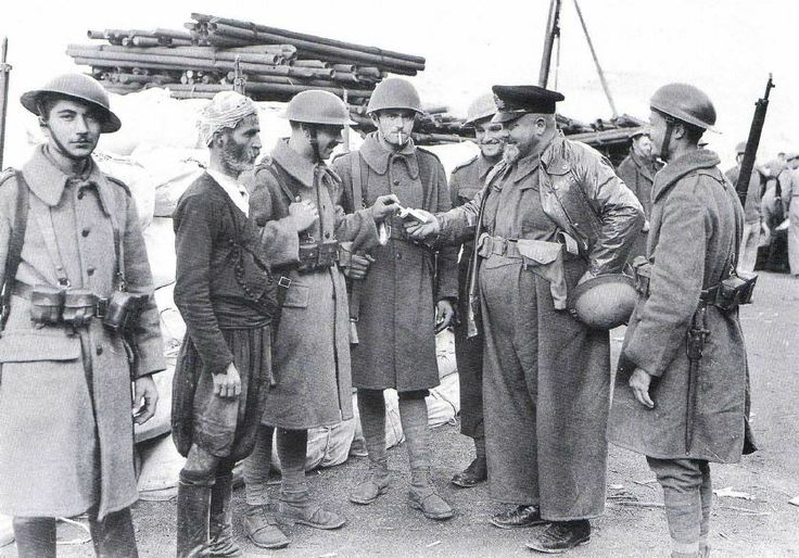 """Caption: """"Greek soldiers mingle with a local civilian on Crete. With more bravery and élan than equipment and training, the Greeks had put up a punishing defense against the paper tiger of an army fielded by the Italians, but were little match for the German attack that followed [in April 1941]. They would put up an equally determined fight to defend Crete when the Germans landed [May-June 1941]."""""""