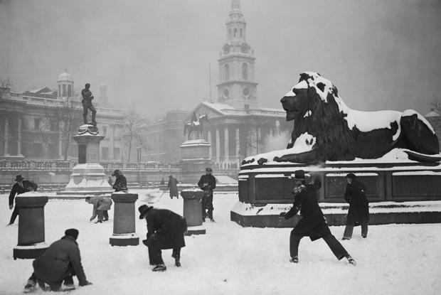 1931: A group of gents enjoy an impromptu snowball fight in the serene and stately setting of a still and snow covered Trafalgar Square, London.