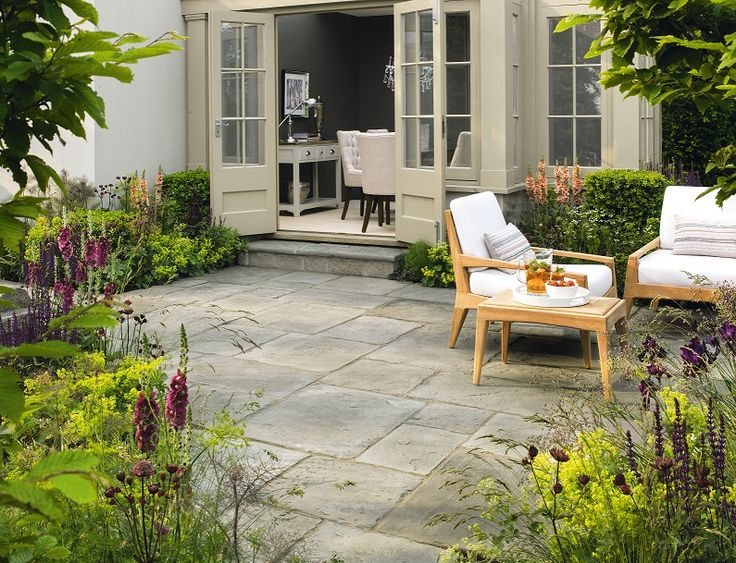 Millstone Paving And Stunning Deep Red Planting Creates An Ideal Setting  For Relaxation.