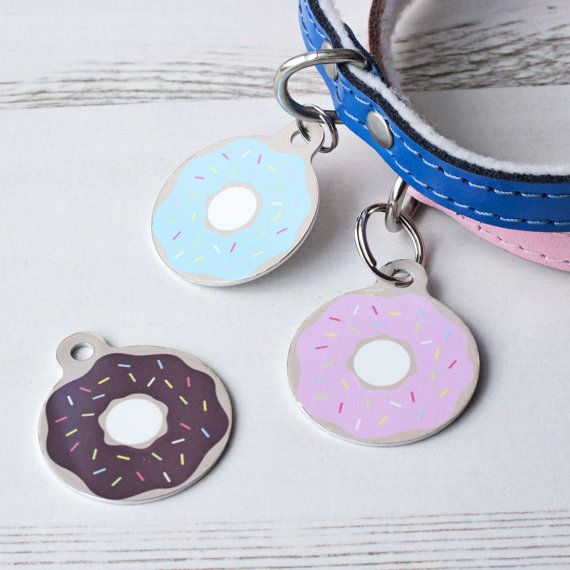 Treat your pet to their own stylish double sided pet ID tag with a donut print. Great for dogs and cats.  Choose from a range of toppings to create a sweet tag for your pet. Our tags are double sided so you can include important details on the reverse of the tag for peace of mind if you and your pet become separated, choose from a range of background colours and the option of black/white text for the reverse. Within the UK, The Control of Dog Act requires dogs out in public places to hav...