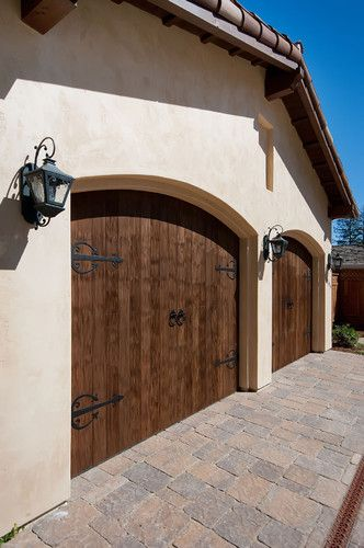 Standard garage doors treated with a faux wood finish and iron embellishments. MUCH less expensive than replacing the garage doors.
