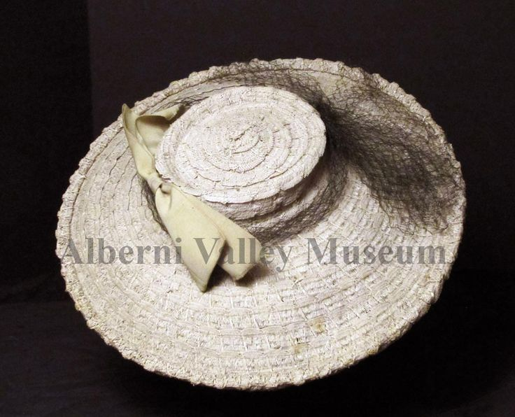 "Beige straw hat with small shallow ""pork pie"" shaped crown and a wide sloping brim turned up at the outer edge. A large grosgrain bow is attached to the front of crown and a dark brown netting encircles the crown. In the late 1930s, hat styles included a type of picture hat with a very shallow crown and a wide brim. These hats were often secured with hat pins.  [Alberni Valley Museum Collection 1971.84.1f]"