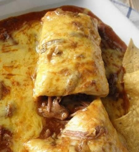 Smothered Beef Burrito: 1 1/2-2 lb stew meat 1 large can enchilada sauce 2 beef bouillon, cubes 1/2 can(s) refried beans 5-7 burrito sized flour tortillas cheddar cheese, shredded 1.In crock pot put beef, enchilada sauce and bouillon and cook on low 7-8 hours (or high 3-4), until beef is fork tender. 2. Add salt if needed. Heat up refried beans and put oven on broil.  3. Roll into burrito and pour enchilada sauce over to completely cover. Sprinkle with cheese and broil until cheese melts.