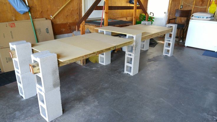 Easy cinder block tables. Perfect for garage sales, using 12 cinder blocks and four 4x4x6 boards and some smaller pressboard for table tops.