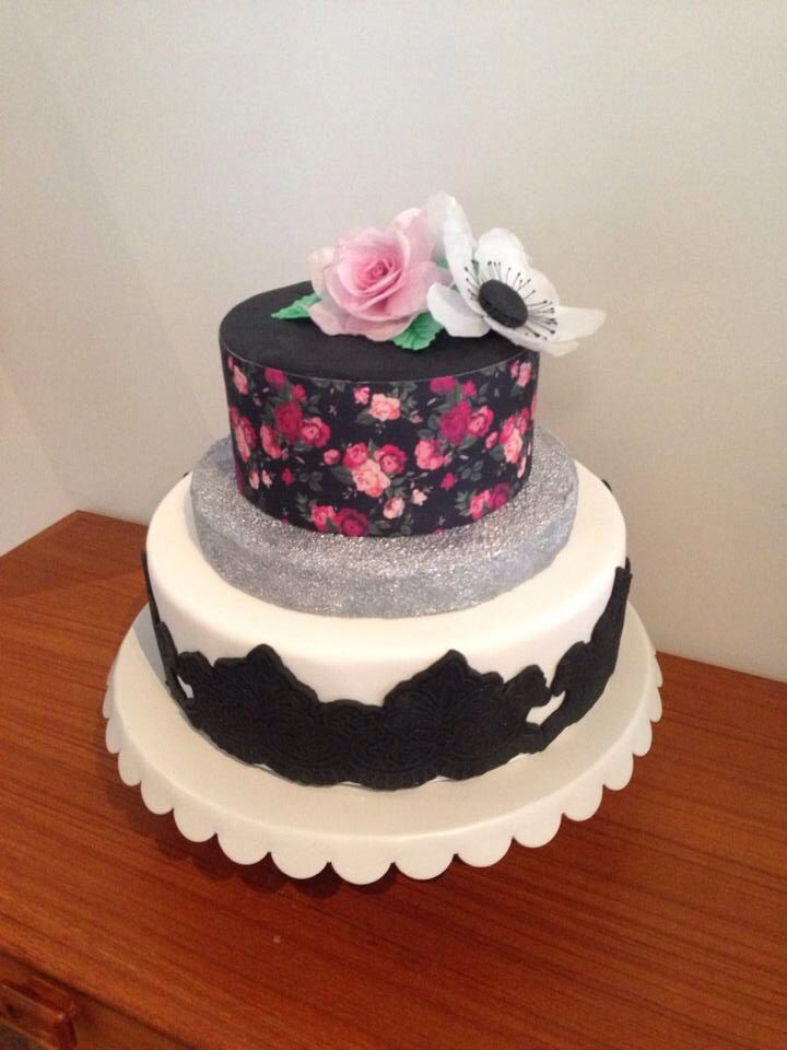 Stunning cake with delicate wafer paper flowers and floral wrap, lace detail and a touch of silver glitter to finish. By Michelle-Marie's Kitchen