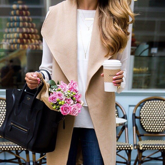 sleeveless camel trench coat, long sleeve white shirt, jeans, and black bag