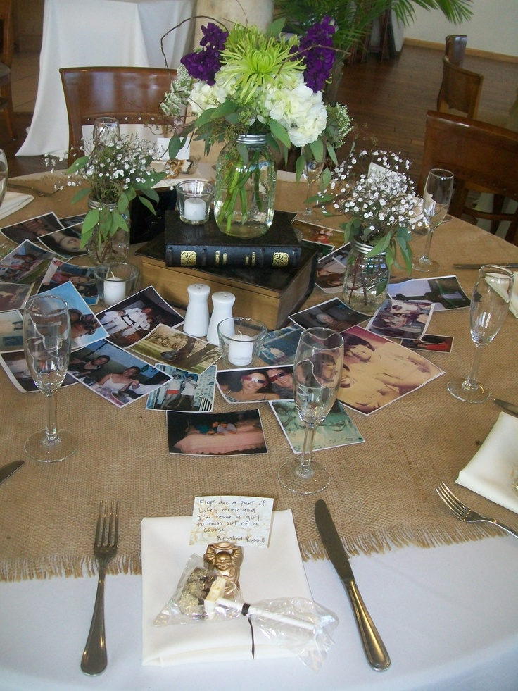 Mason Jar Centerpiece on top of Dark Brown Stacked Books with Babies Breath Filled Mason Jar Accents.  Very Down to Earth.