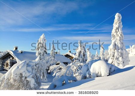 Cottages on snowy mountain on a sunny cold winter day on tourist resort in Lapland Finland. Cottages and spruce trees are covered by heavy snow.  - stock photo