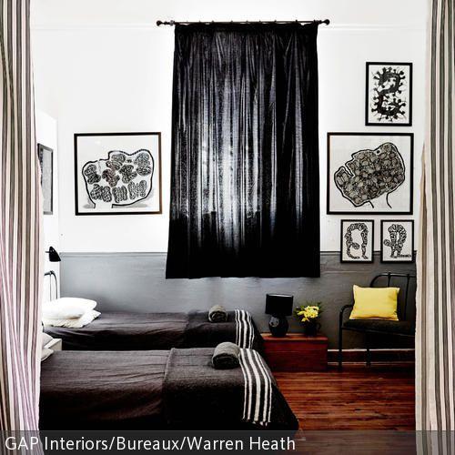 Der dunkle Holzboden in Verbindung mit den schwarz-weißen Elementen wie Bett, Vorhang und Wandbildern erzeugt einen harmonischen Gesamteindruck. Das gelbe  …