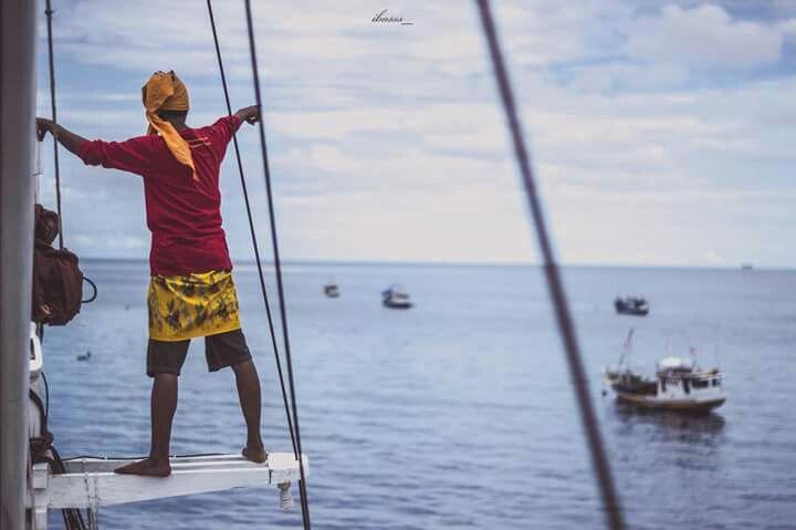 """Perahu Phinisi, Pulau Sanane. """"Turunkan jangkar, kita berlabuh sejenak di sini"""". Gulung semua layar, kabarkan kepada kapal lain, sebentar lagi cuaca buruk akan menguji. Di belakang sana, awan hitam telah berarak di kaki langit. Di depan sana, dermaga kecil menunggu di pulau Badi'. Dahulu kita bahkan sering menari dalam badai. Sekarang ketika badai datang kita harus ambil diri."""