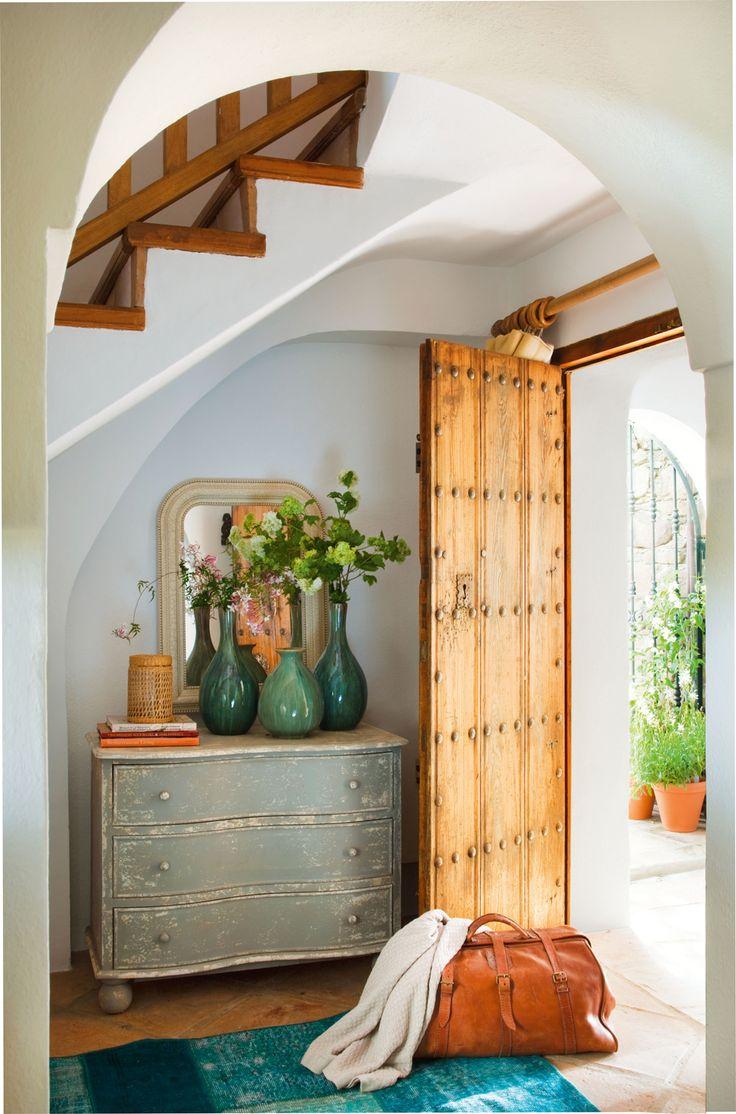 Recibidor rústico con puerta de madera, cómoda pintada y alfombra azul (00345177)