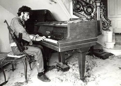 A Lebanese fighter plays the piano in a house his forces have recently taken over during the 1975-90 civil war.