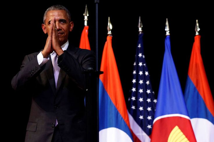 President Barack Obama holds his hands together and bows at the end of…