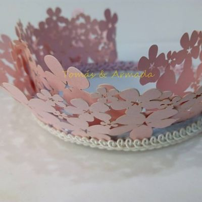 Tocado de niña en forma de corona. Flores troqueladas de color rosa en cartulina nacarada