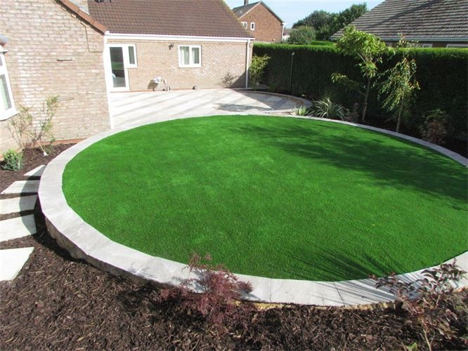 Circular raised lawn with patio and border