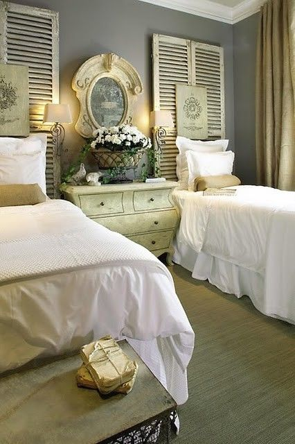 Sweet, crisp and dressy white linens with frilly pillows make a nice contrast with the distressed and primitive shutters being used as head boards.