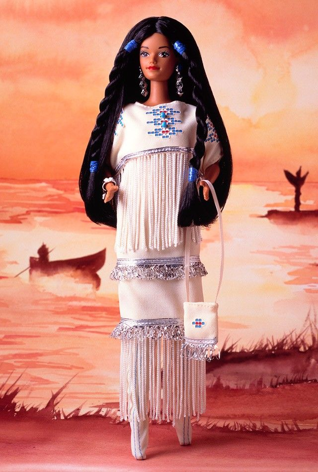 ative American Barbie doll is part of a proud Indian heritage, rich in culture and tradition. Her tribe-inspired costume is a white dress decorated with Indian artwork, fringe, and complemented by the soft faux leather moccasins on her feet. Her purse is also decorated with fringe. Indian women often wear their hair in braids, like this doll, tied at each end with blue bands.: Barbie S, Barbies, Fashion Dolls, Barbie Collection, Barbie Dolls, Doll 1St, American Barbie, Native American