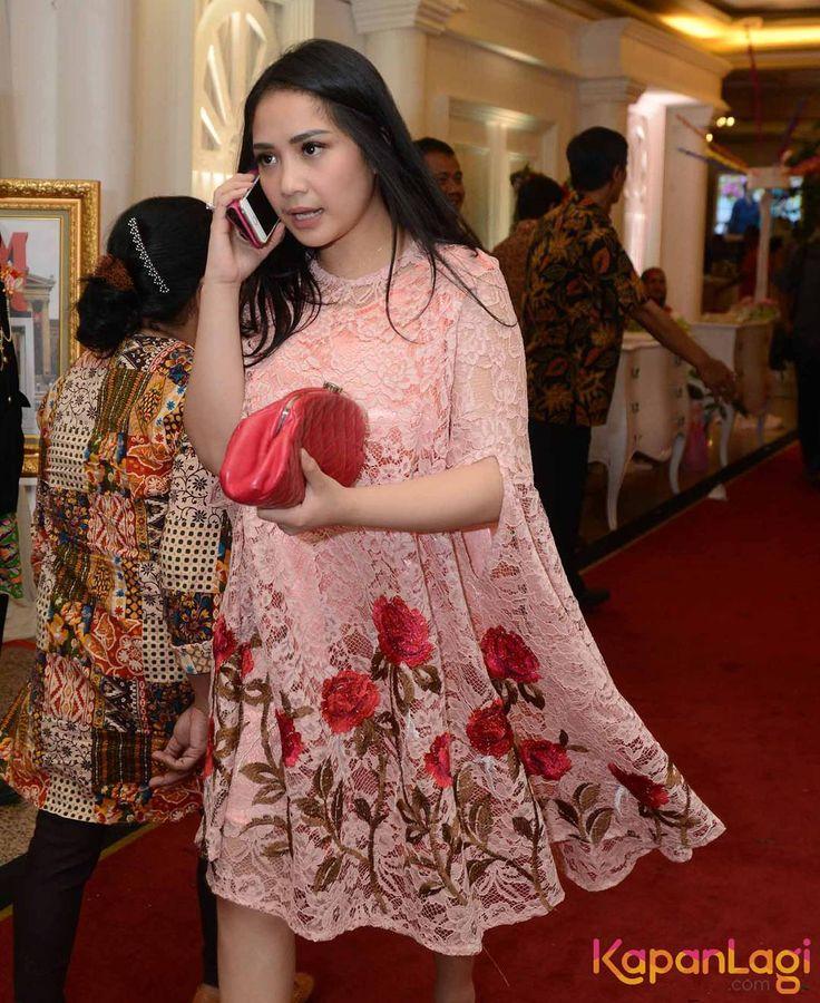 Nagita Slavina tampil anggun dengan dress warna merah muda bermotif bunga-bunga....