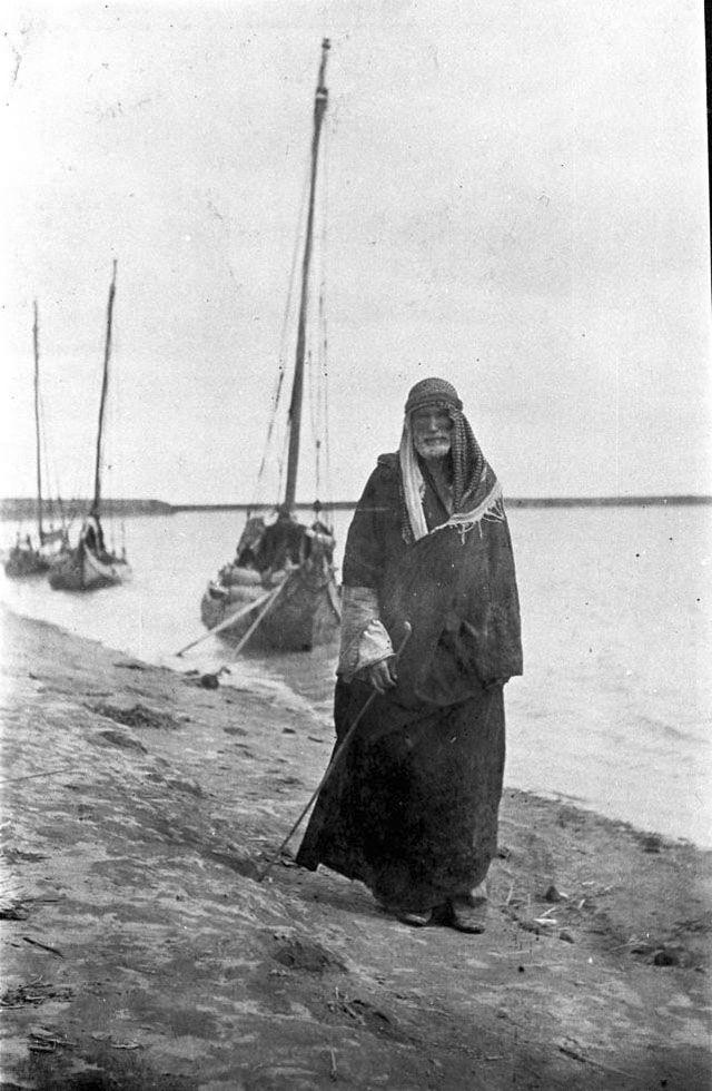 March 1918, Gertrude Bell, Saiyid Mashkhur - Iraq Saiyid Muhammad al Mashkhum [Arab man standing at riverside, dhows moored in background]