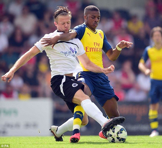 Wrestle: Boreham Wood's Matthew Whichelow and Arsenal's Chuba Akpom go for the ball...