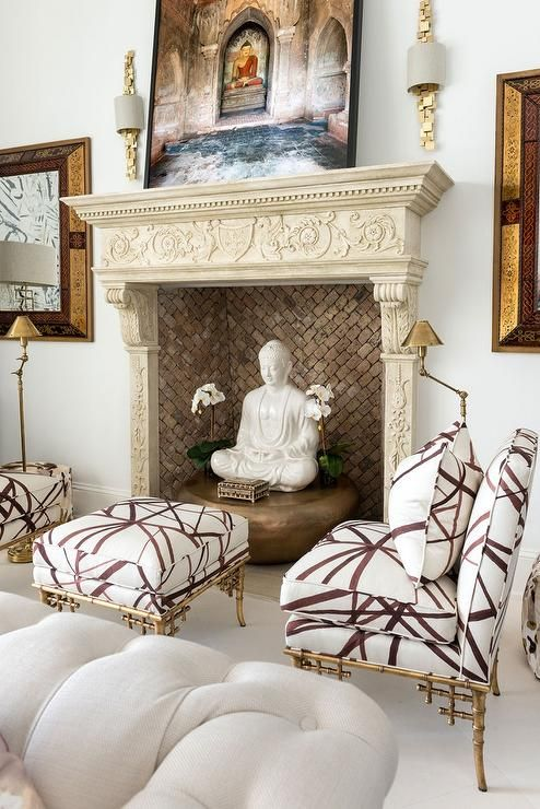 Gorgeous conversation area in front of ornate fireplace features a pair of gilt bamboo slipper chairs upholstered in Kelly Wearstler Channels Fabric Taupe Ivory centered on a matching ottoman flanked by a pair of swing arm antique brass floor lamps.