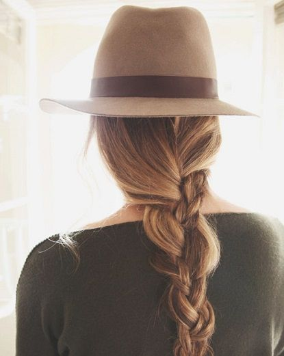 Style a fedora with a loose braid for a pretty look