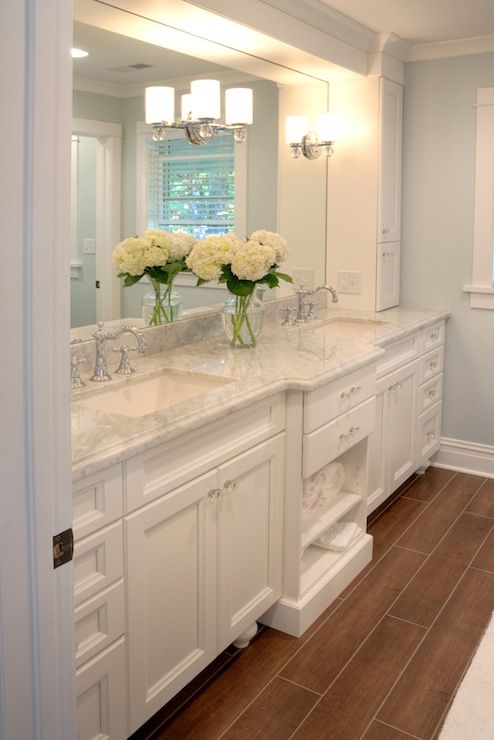 White bathroom with Carrera marble counters, open towel storage.