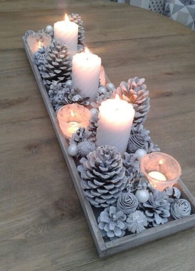 Pine cones, pearls, pillar candles and frosted candle holders with tea lights in a white wooden holder.