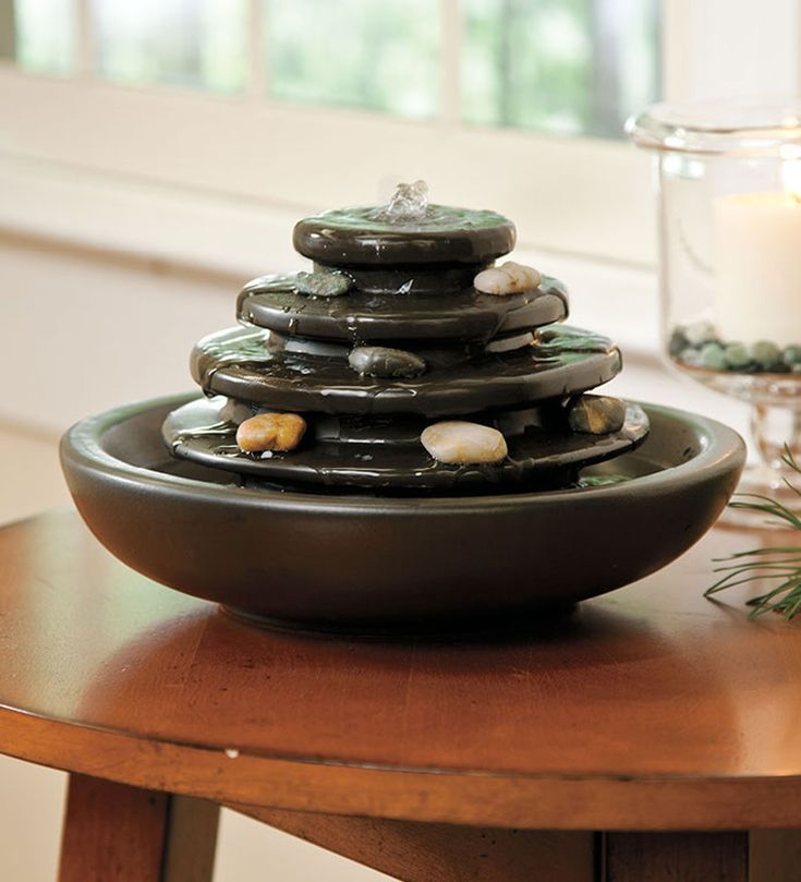 Add the soothing sight and sound of water to your interior space with this 5-Tier Ceramic Tabletop Fountain With Pebbles