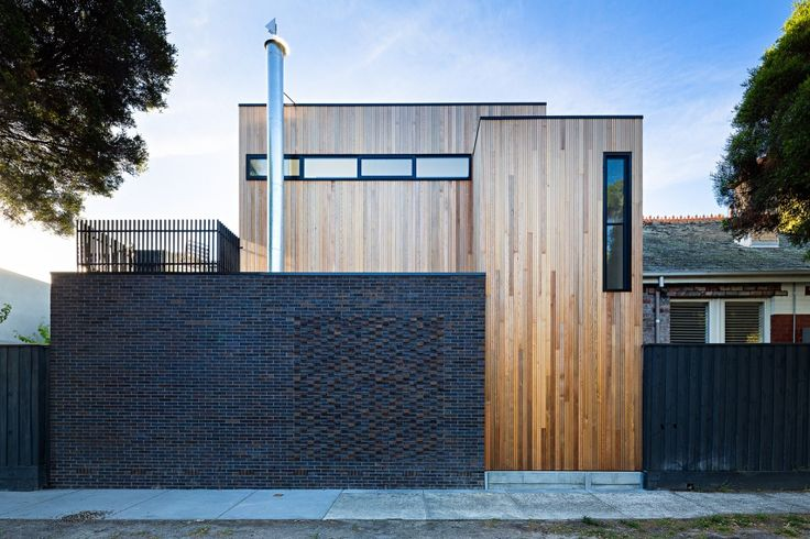 Modern rustic facade on this home: dark, horizontal brick next to medium-toned, vertical wood planks || Elwood House / Robert Nichol & Sons