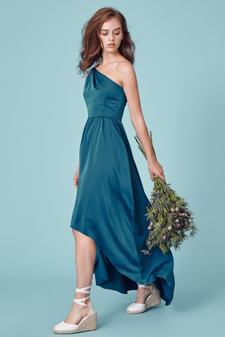 TIA is a draped one shoulder maxi dress with an asymmetric hem detail and subtle gold accents.