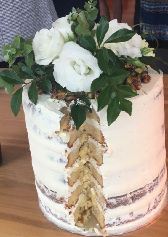 Naked Cake (cut open) White Chocolate Mud Cake Vanilla Bean Buttercream Honey coated pistachio nuts Flower arrangement