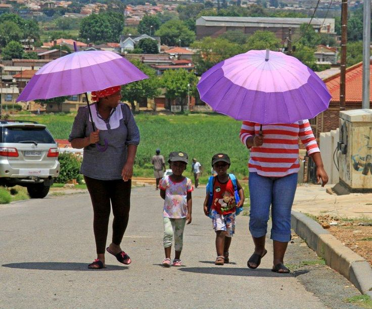 My photojournalist style tour of Soweto & Other Townships, lets my visitors experience themes such as this one on the lookout to photograph people with umbrellas.  Makes the tour fun and interesting. Photo by Ilan Ossendryver