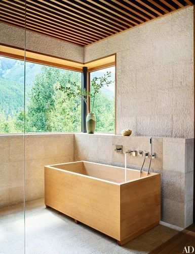 The centerpiece of the master bath at an Aspen, Colorado, home by designer Shawn Henderson and architect Scott Lindenau is a custom-made Japanese soaking tub with Dornbracht fittings. The walls are paneled in Yangtze River limestone | archdigest.com
