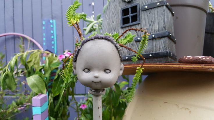 Garden art.  I made this with an old dolls head, painted to look like concrete, antiqued and planted with succulents.