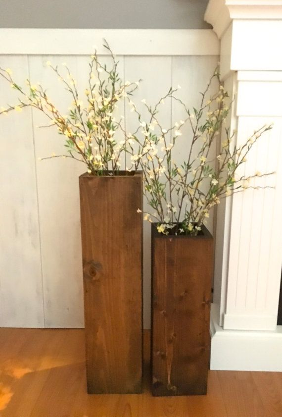This set of 2 large floor vases will add a little rustic charm to your porch or living room! The large vase measures 24 x 6 and the smaller one measures 18 x 6. These vases are made form reclaimed wood that has been sanded and stained a dark walnut. Looks great with large stems or branches