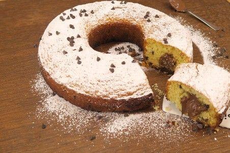 Il ciambellone dal cuore morbido è un dolce molto goloso, si prepara in poco tempo e conquisterà senza dubbio ogni bimbo!   GLI INGREDIENTI 3 uova 220g di zucchero 220g di farina 1 pizzico di sale 1 bustina di lievito per dolci 100g di burro 200g di gocce di cioccolato crema di nocciole q.b.  LA PREPARAZIONE Sbattete le uova insieme al sale e lo zucchero. Poi aggiungete il burro, la farina e infine il lievito. Quando il composto sarà raddoppiato e bello spumoso, aggiungete le gocce di…