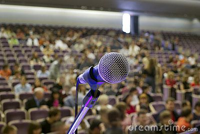 Stock Photo: Illuminated microphone on the stage and auditorium